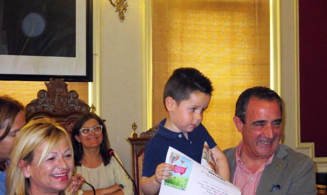 Juani Sorio y Manuel Mínguez con uno de los niños premiados